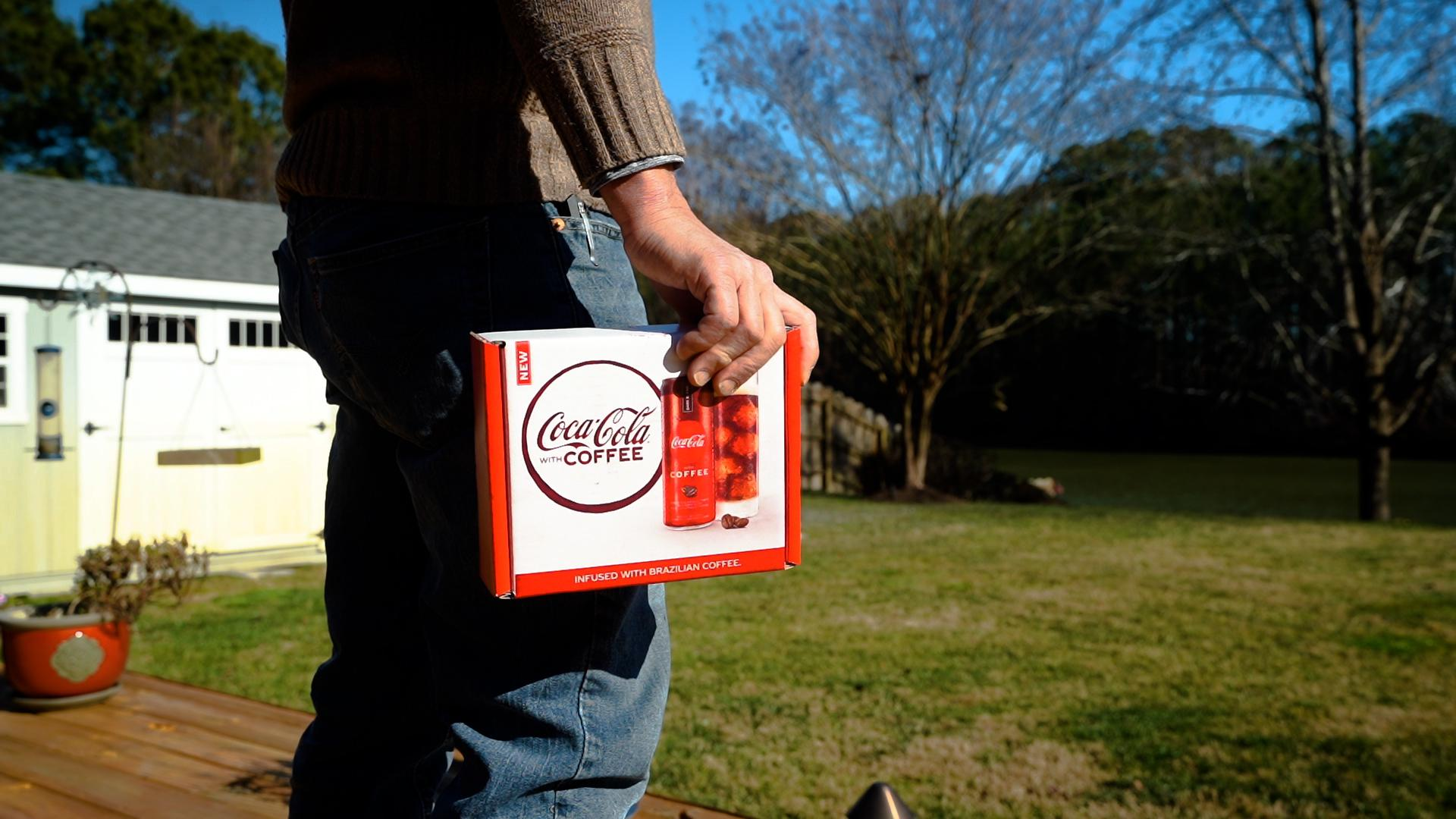 Consumer holding a box of Coca-Cola with Coffee