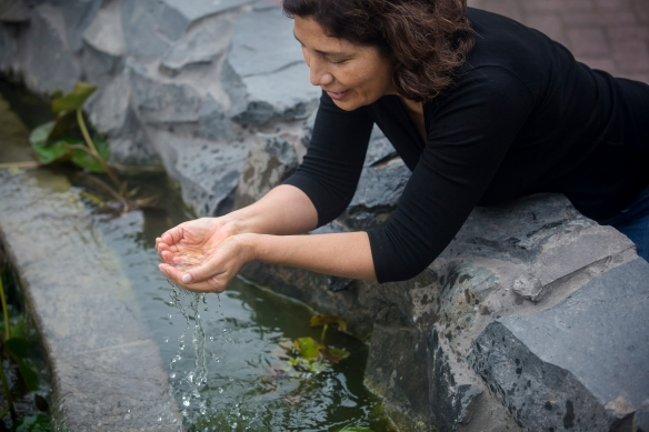 A woman cupping water in her hands